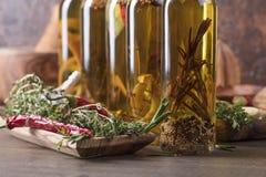 Бутылки оливкового масла с warious специями и травами Стоковые Изображения