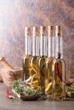Бутылки оливкового масла с warious специями и травами Стоковое Изображение