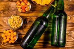 2 бутылки пива и различных закусок на деревянном столе верхняя часть VI Стоковое Фото
