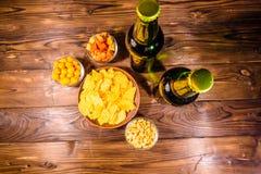 2 бутылки пива и различных закусок на деревянном столе верхняя часть VI Стоковое Изображение RF
