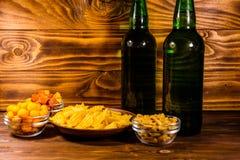 2 бутылки пива и различных закусок на деревянном столе Стоковое Изображение RF