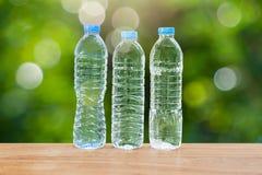 3 бутылки питьевой воды на деревянном столе на запачканной зеленой предпосылке bokeh Стоковая Фотография RF