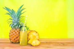 Бутылки сока ананаса с отрезанным ананасом приносить на древесине Стоковая Фотография RF