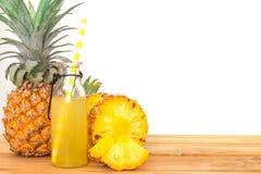 Бутылки сока ананаса с отрезанным плодоовощ ананаса на древесине Стоковая Фотография