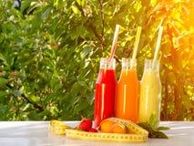 3 бутылки сока, плодоовощей и измеряя ленты на зеленой предпосылке, концепции еды стоковое фото rf