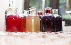 Бутылки с домодельными тинктурами и стекла на таблице Стоковое Фото