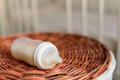Бутылки с молоком для младенца на корзине соломы Стоковая Фотография