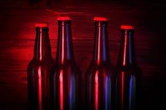 Бутылки с пивом на коричневой деревянной предпосылке Стоковые Фотографии RF