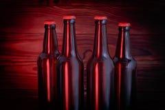 Бутылки с пивом на коричневой деревянной предпосылке Стоковые Фото