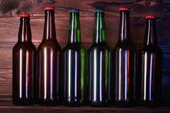 Бутылки с пивом на коричневой деревянной предпосылке Стоковое Изображение