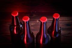 Бутылки с пивом на коричневой деревянной предпосылке Стоковое Изображение RF