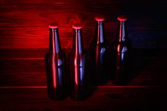 Бутылки с пивом на коричневой деревянной предпосылке Стоковая Фотография RF