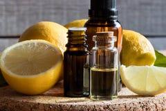 Бутылки эфирного масла лимона с лимонами Стоковое Фото