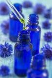 Бутылки Tranparent стеклянные с жидкостью падений необходимой в капельнице на деревянной предпосылке с целебными цветками Стоковые Изображения RF