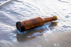 Бутылочное стекло на пляже песка с морем или океаном Стоковое Изображение