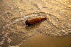 Бутылочное стекло на пляже песка с пеной воды моря или океанской волны Стоковые Изображения RF