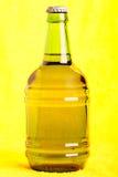 бутылочный зеленый пива над желтым цветом Стоковое Изображение