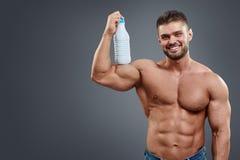 Бутылка атлетического фитнеса человека модельная держа стоковое фото rf