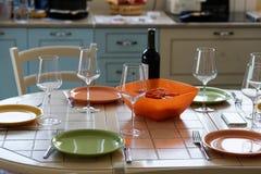 Бутылка вина, бокалы и пустые плиты на таблице Стоковые Фотографии RF