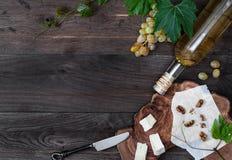 Бутылка вина, свежей виноградины, сыра и грецкого ореха на деревянной предпосылке Стоковые Фотографии RF