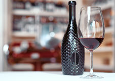 Бутылка вина стоя на таблице с стеклом Стоковые Изображения