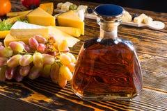 Бутылка вискиа на таблице с сыром и виноградинами Стоковые Изображения RF