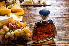 Бутылка вискиа на таблице с сыром и виноградинами Стоковое Фото