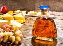 Бутылка вискиа на таблице с сыром и виноградинами Стоковые Фото