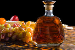 Бутылка вискиа на таблице с сыром и виноградинами Стоковое фото RF