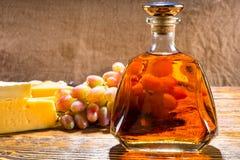 Бутылка вискиа на таблице с сыром и виноградинами Стоковая Фотография