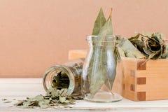 Бутылка высушенных листьев залива и деревянной коробки с селективным фокусом o Стоковые Изображения RF