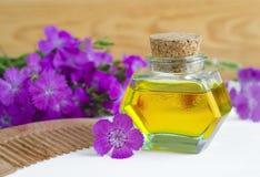 Бутылка естественного косметического масла и деревянного гребня волос Стоковые Фотографии RF