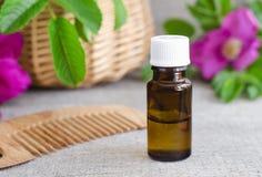 Бутылка естественного косметического (необходимого) масла ароматности и деревянного гребня волос Стоковое Изображение