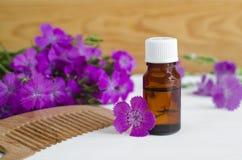 Бутылка естественного косметического (необходимого) масла ароматности и деревянного гребня волос Стоковое фото RF