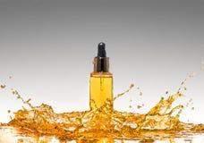 Бутылка желтой косметики в большом выплеске масла на предпосылке серого цвета градиента Стоковая Фотография