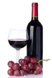 Бутылка и бокал вина с красными виноградинами Стоковые Фотографии RF