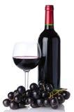 Бутылка и бокал вина с черными виноградинами Стоковое фото RF
