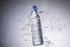 Бутылка и вода брызгают изолированный на белой предпосылке Стоковые Фотографии RF