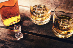 Бутылка и стекла вискиа с льдом на темном деревянном столе Стоковая Фотография