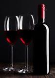 Бутылка и стекла красного вина на деревянном столе чернят Стоковые Изображения RF