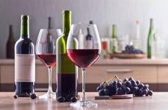 Бутылка и стекла красного вина на кухонном столе Стоковое Изображение RF