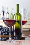 Бутылка и стекла красного вина на кухонном столе Стоковые Фото