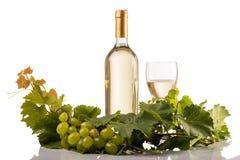 Бутылка и стекло белого вина на белой предпосылке с листьями и виноградинами лозы Стоковое Изображение RF