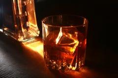 Бутылка и стекло вискиа или бербона с льдом на черной каменной таблице Стоковая Фотография