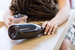 Бутылка и стекло в руках пьяной женщины стоковое изображение