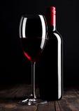 Бутылка и стекло красного вина на деревянном столе чернят Стоковые Фотографии RF