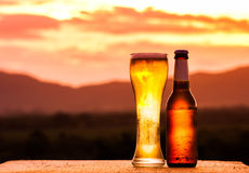 Бутылка и стекло светлого пива на заходе солнца Стоковые Изображения