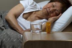Бутылка медицины и вода при старшая женщина спать в backg Стоковая Фотография