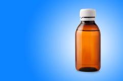 Бутылка медицины коричневой пластмассы на голубой предпосылке Стоковое Изображение