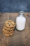 Бутылка молока с печеньями обломока шоколада Стоковая Фотография